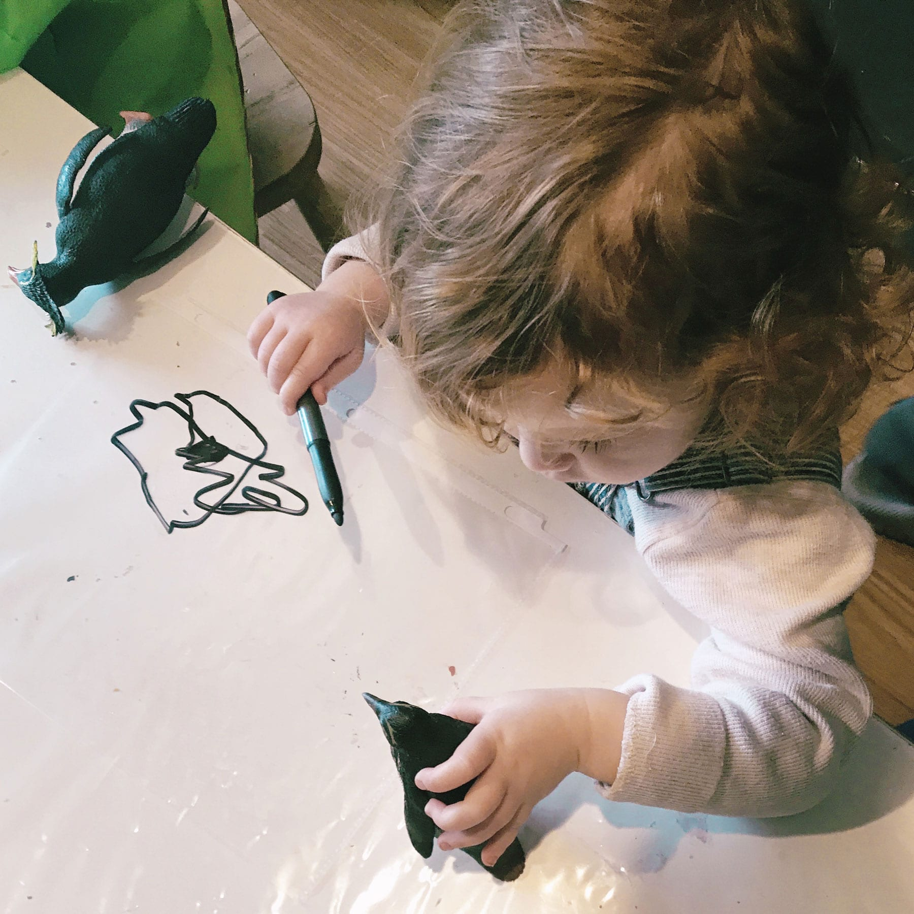 a toddler draws with a marker while holding a penguin toy at Scuola Creativa