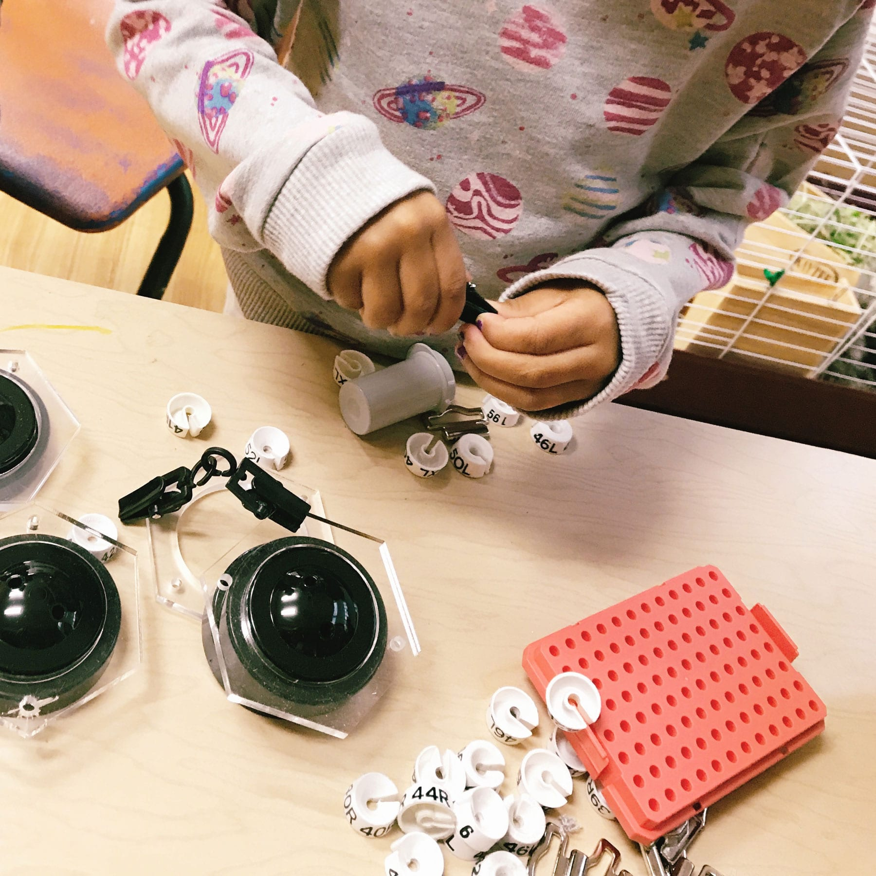 a closeup of a girl manipulating loose parts at Scuola Creativa
